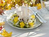 Herbstliches Gedeck mit Stoffserviette und Blumenkranz