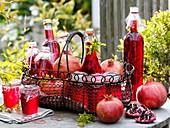 Granatapfelsaft, Granatapfelgelee und frische Granatäpfel auf Gartentisch