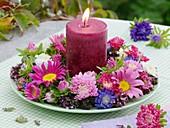 Kerze mit Kranz aus Sommerastern und Oregano auf Teller