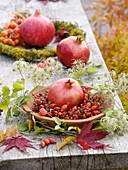 Pomegranate in rose hip wreath, clematis seed heads, autumn leaves