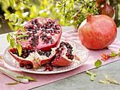 Aufgeschnittener Granatapfel auf Teller, daneben ganze Frucht