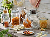 Assorted dried fruit in storage jars on wooden table