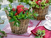 Strawberries and fresh mint in wicker baskets