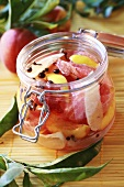 Spicy bottled peaches in preserving jar