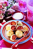 Plum dumplings on coloured plate