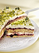 Quark cake with redcurrant jelly and pistachios, a piece cut