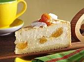 Piece of cheesecake with apricots and coconut shavings