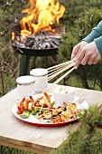Barbecued prawn skewers on wooden table beside barbecue