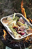 Barbecued onions and fennel marinated in wine, on barbecue