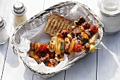 Barbecued mixed kebabs with bread in bread basket