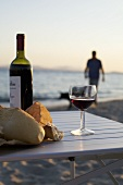 Red wine and bread on table by sea, person in background