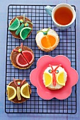Butterfly and beetle cakes with chocolate, cream and jelly fruit slices