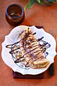 Pancake with nut filling and chocolate sauce