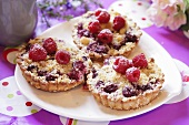 Fruit crumble tarts topped with fresh raspberries