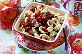 Pasta shells with cherries and pomegranate seeds