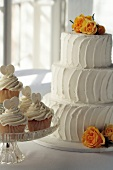Three-tiered white wedding cake and lemon cupcakes
