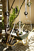 Small wreaths hanging above wheelbarrow holding ice cubes & wine bottles