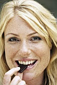 Blond woman eating a piece of chocolate