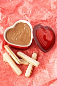 Chocolate mousse in heart-shaped dish, sponge fingers