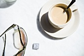 Milky coffee and sunglasses on table