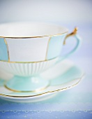 Gold-rimmed teacup and saucer