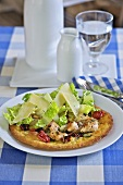 Pizza topped with chicken, romaine lettuce and cheese