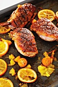 Roast duck breasts with orange slices and kumquats on baking tray