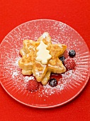 Star-shaped pancakes with butter, berries and maple syrup