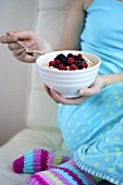 Woman eating muesli with berries