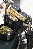 Bean & quinoa salad & sardine spread sandwiches in food carriers on motorbike