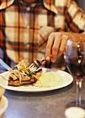 Mensch beim Essen eines Hähnchengerichts