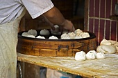Asian pastry parcels being placed in giant steaming basket