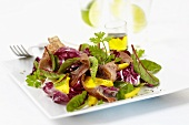 Mixed salad leaves with mango wedges