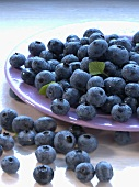 Blueberries on and in front of a plate