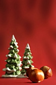 Three hazelnuts lying in front of artificial fir trees