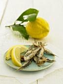 Deep-fried sardines with lemon wedges