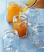 Orange and Campari jelly being poured into jam jars