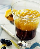 Blackberry and apricot jam layered in a glass