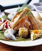 Plate of Asian appetisers with pasta and pastry parcels