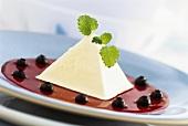 Pyramid-shaped cream dessert on hibiscus flower sauce