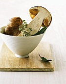 Halved cep with thyme and sage in a bowl