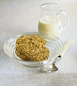 Two wheat biscuits (Weetabix) in a bowl, milk behind