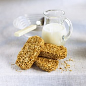 Three wheat biscuits (Weetabix) in front of a carafe of milk