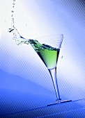 Green cocktail splashing out of a glass