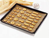 Assorted piped biscuits on a baking tray