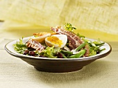 Salad with fried bacon and soft-boiled eggs