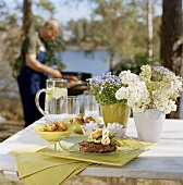 Barbecued dishes on garden table, man barbecuing behind