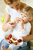 Small child eating strawberries with its mother