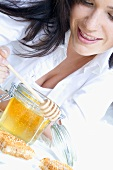 Young woman with honey, honey dipper and honeycomb