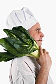 Chef with knife in his mouth and chard on his shoulder